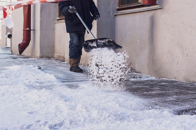 Adult man shoveling snow from city streets