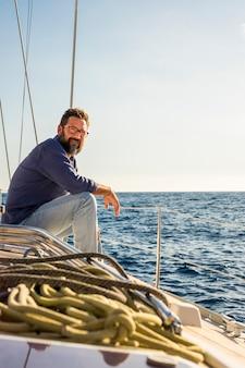 大人の男が旅行を楽しんで帆船の甲板に座る