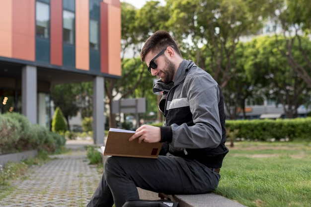 Adult man sitting on bench and learning