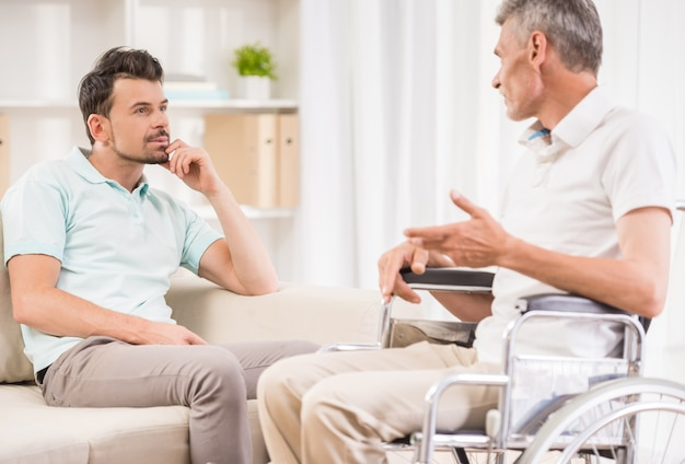 Adult man sitting at home and talking to his eldery father.