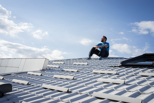Adult man sitting on house roof and contemplating