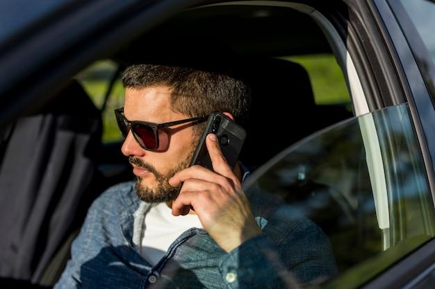 大人の男が車の中で座っていると電話で話しています。