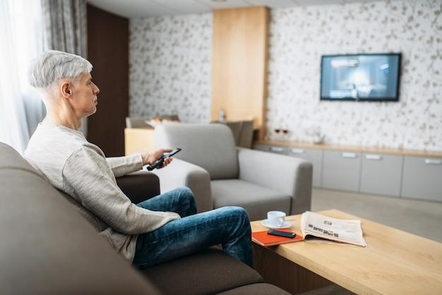 소파에 앉아 집에서 tv를 시청하는 성인 남자. 청바지에 성숙한 남성 사람이 거실에서 휴식
