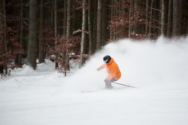 Взрослый мужчина катается на лыжах во время скоростных гонок по горному склону