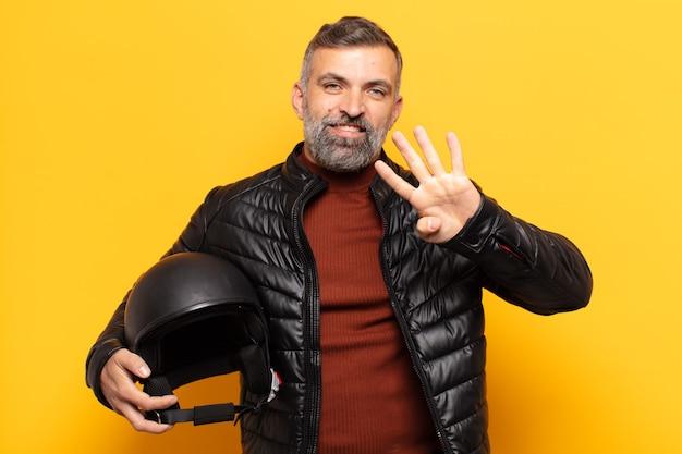 Взрослый мужчина улыбается и выглядит дружелюбно, показывает номер четыре или четвертый с рукой вперед, считая