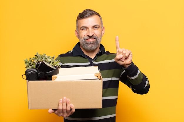 Взрослый мужчина улыбается и выглядит дружелюбно, показывает номер один или первый с рукой вперед, отсчитывает