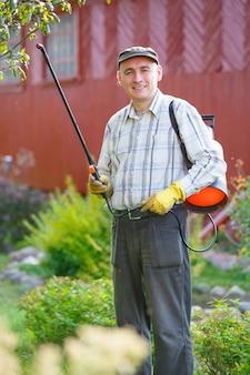 정원에서 관목을 살포하는 성인 남자