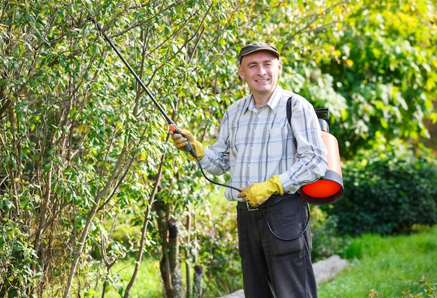 성인 남자는 정원에서 녹색 부시 뿌리