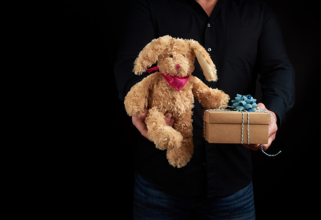 Adult man stands on dark wearing a black shirt and holds in his hand a brown cardboard box with a gift and a cute brownã'âbunny toy