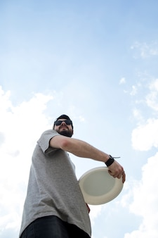 Adult man in sunglasses holding frisbee disc