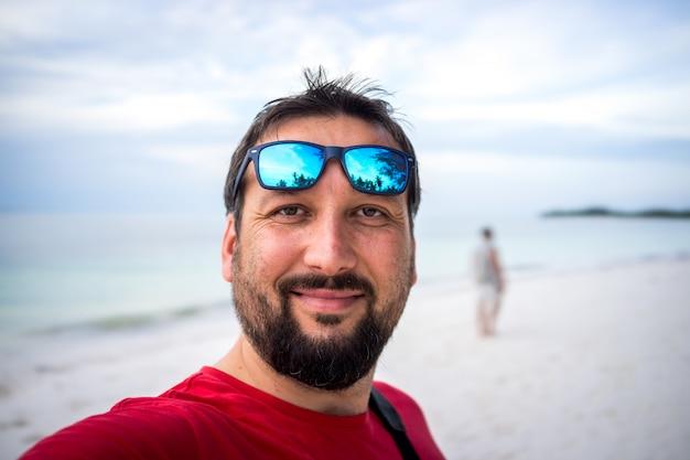 Adult man taking selfie on tropical beach