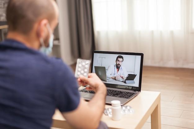 Взрослый мужчина разговаривает с врачом о своем лечении во время глобальной пандемии.