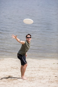 Adult man throwing frisbee disc on beach