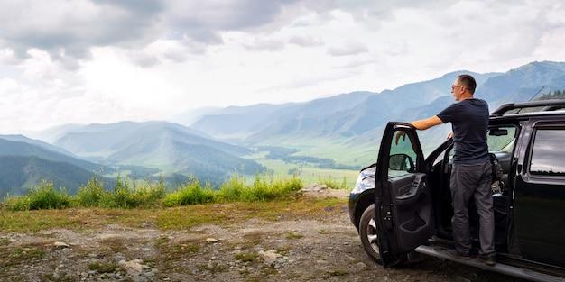 山の背景を持つ車の上に立っている大人の男性旅行者