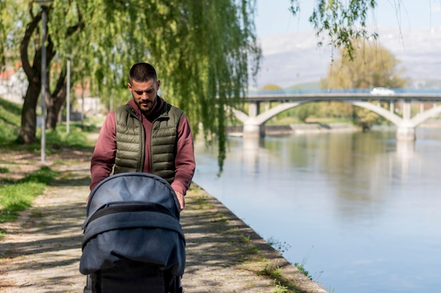 Adult man walking with baby stroller near river