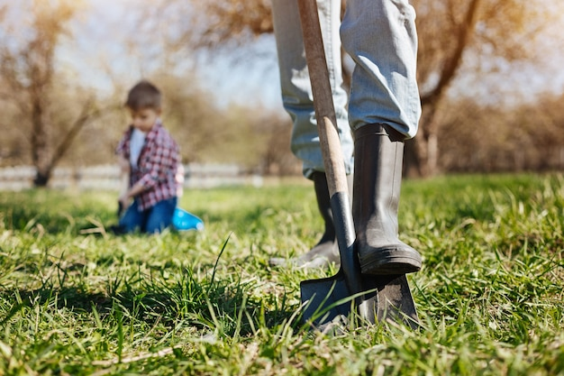 Adult man wearing green wellies digging the soil with a shovel while spending free time outside with his grandson