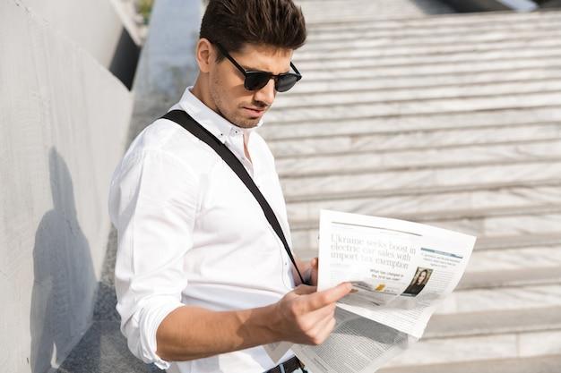 Взрослый мужчина в солнечных очках, пьющий кофе на вынос и читающий газету, стоя у стены на открытом воздухе