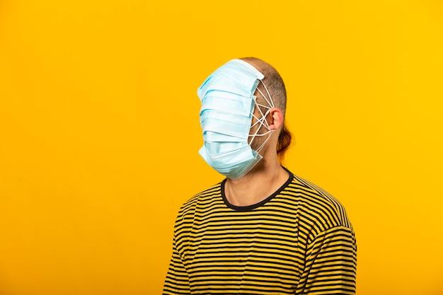 黄色の背景に対して彼の顔全体を覆う手術用フェイシャルマスクを身に着けている成人男性