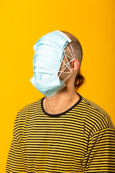 Adult man wearing surgical facial masks covering all his face against a yellow background