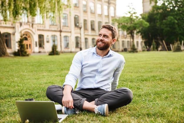 Adult man wearing white shirt, sitting on grass in park with legs crossed while working on silver laptop