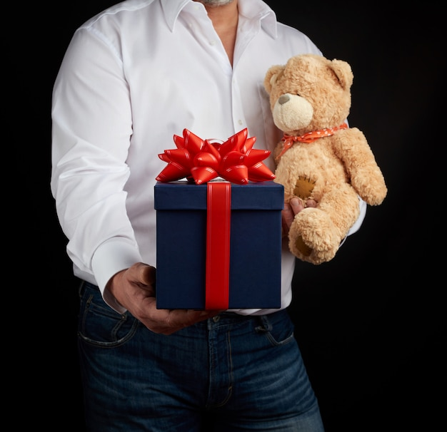 Adult man in a white shirt holds a blue square box tied with a red ribbonnd brown teddy bear