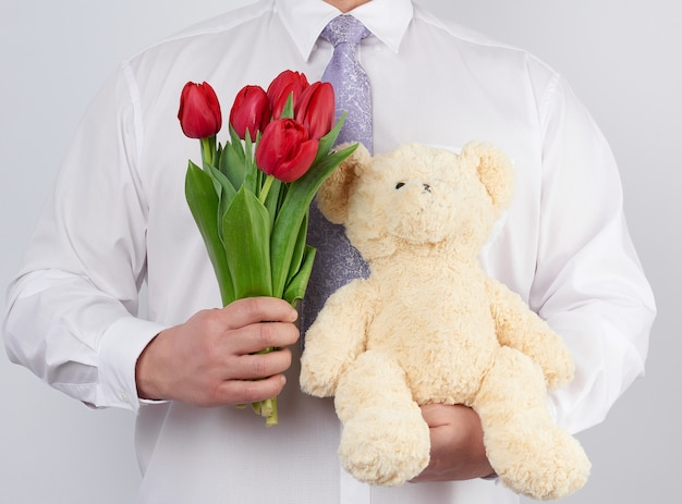 Adult man in a white shirt holds a bouquet of red blooming tulips and a white teddy bear