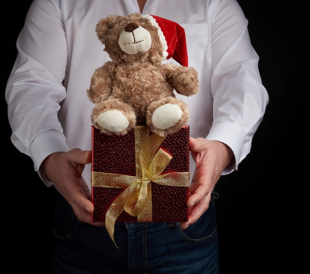 Adult man in a white shirt holds a red square box tied with a golden ribbon and brown teddy bear