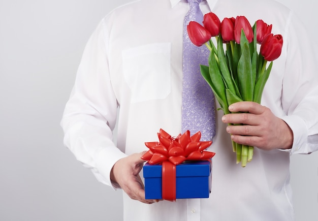 Adult man in a white shirt and a lilac tie holding a bouquet of red tulips with green leaves and gift box on a white background, concept for happy birthday, anniversary, valentines day