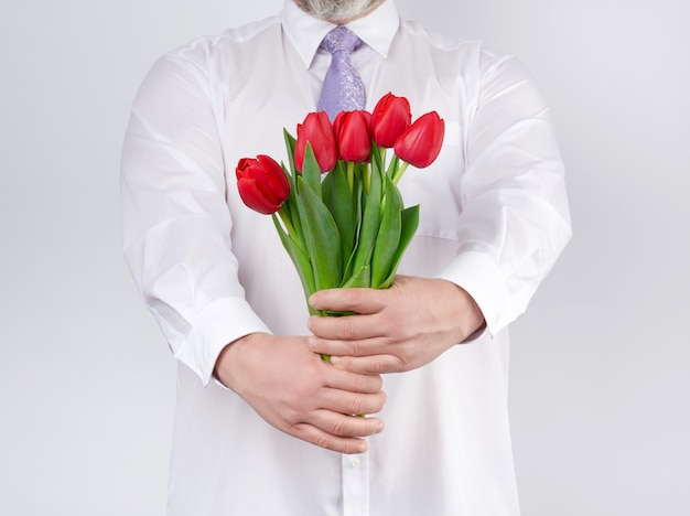 Adult man in a white shirt and a lilac tie holding a bouquet of red tulips with green leaves