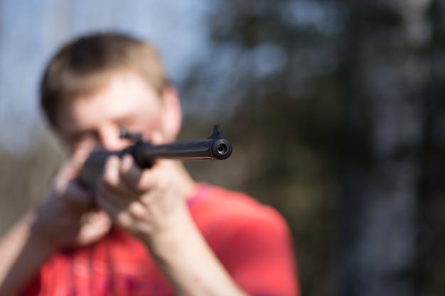 Взрослый человек с пневматическим пистолетом в лесу