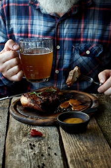 Adult man with a beard eats mustard steak and drinks beer