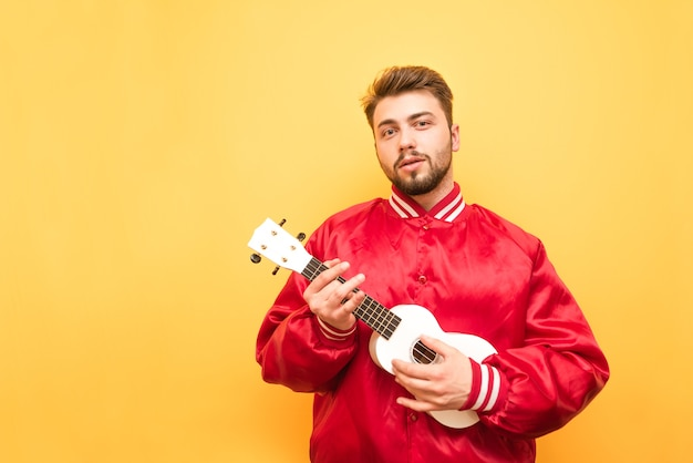 Adult man with a beard is standing on yellow with ukulele in his hands