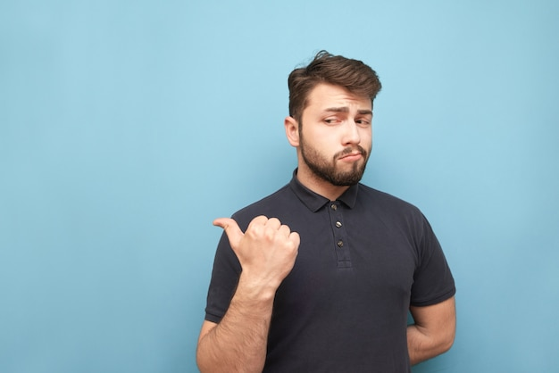 Adult man with a beard stands on blue, looks thoughtfully to the side and throws his finger into an empty space