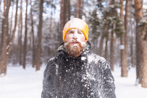 An adult man with a beard in a winter forest all face in the snow, frozen, unhappy with the cold