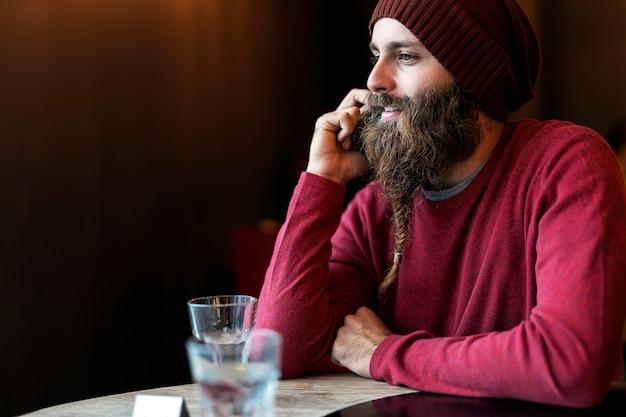 전화로 말하는 동안 커피 한잔 마시고 카페에 앉아 꼰 수염을 가진 성인 남자