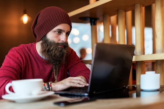 노트북에 입력하는 동안 커피 한잔 마시고 카페에 앉아 꼰 수염을 가진 성인 남자