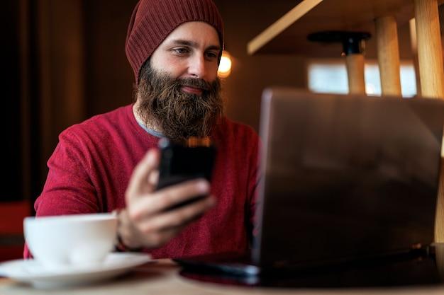 노트북에 입력하는 동안 전화 커피 한잔 마시고 카페에 앉아 꼰 수염을 가진 성인 남자