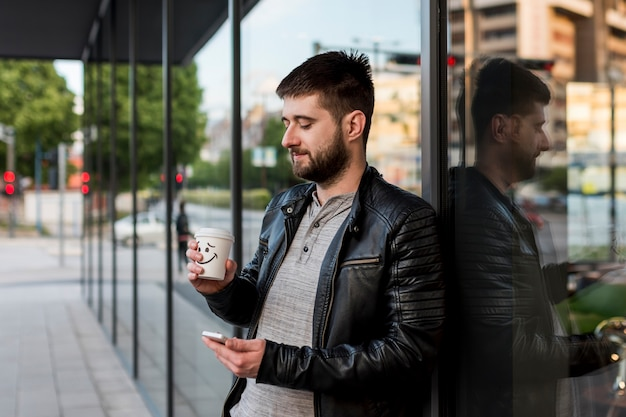 Adult man with coffee and smartphone standing outside