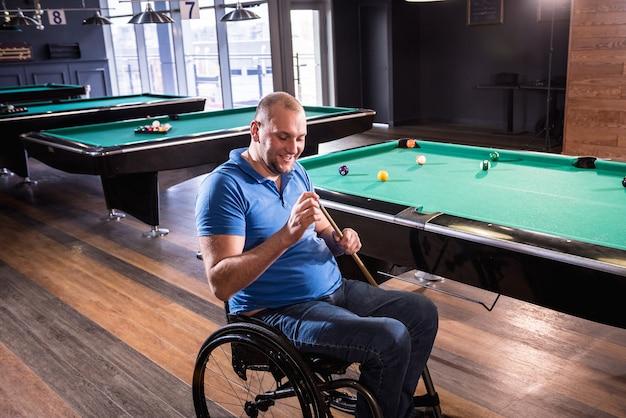 Взрослый человек с ограниченными возможностями в инвалидной коляске играет в бильярд в клубе
