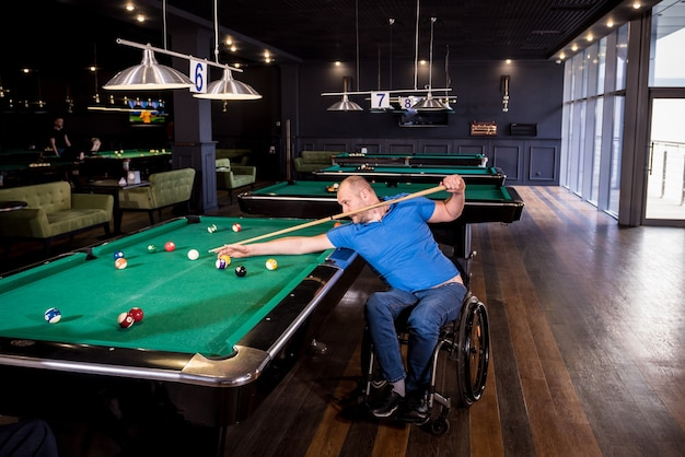 Adult man with disability in a wheelchair play billiards in the club