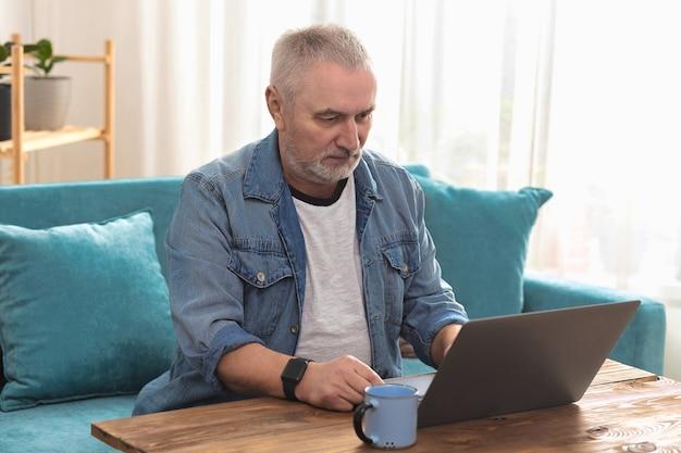 Взрослый мужчина с седыми волосами сидит на диване у себя дома и работает на ноутбуке