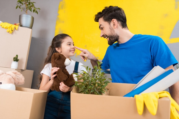 Adult man with little girl, dismantles boxes of things.