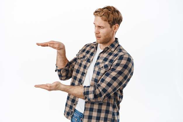 Adult man with red hair and beard, holding something empty space, looking at hands displaying an item with confused face, standing over white wall