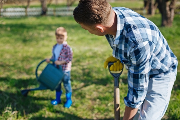 Adult man with a spade watching his adorable child watering a green vernal lawn with a pouring can while gardening together