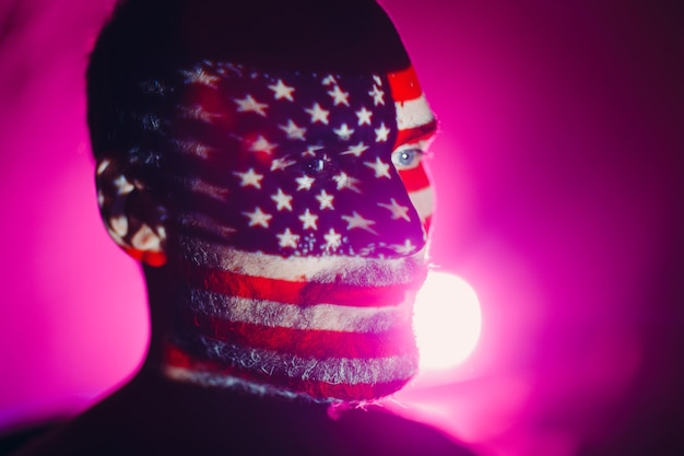 Adult man with usa flag on his face in the dark.