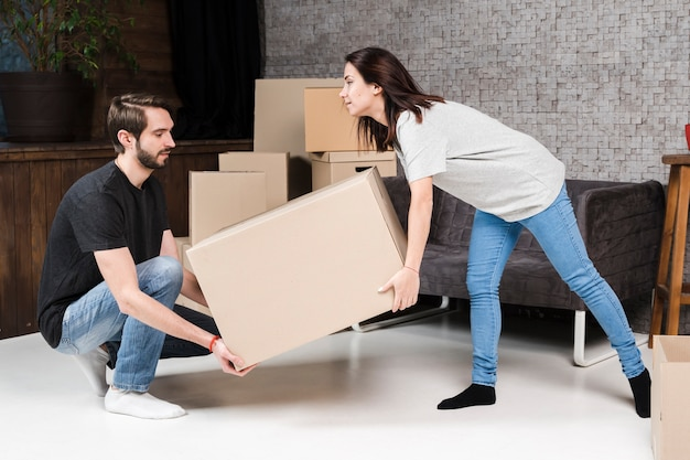 Adult man and woman carrying cardboard boxes