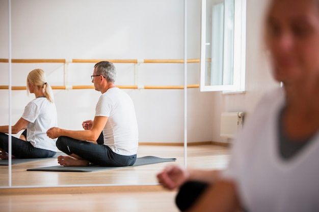 Adult man and woman meditating yoga
