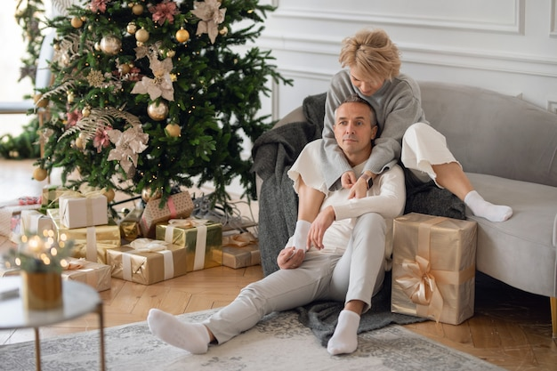 Adult man and woman sit on the sofa near the christmas tree and hug