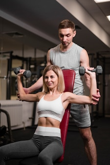 Adult man and woman working out at the gym