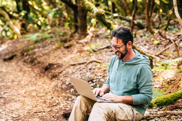 緑の野生の森の真ん中で大人の男がコンピューターのラップトップで動作します